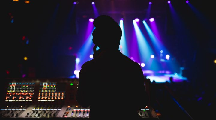 The silhouette of an audio engineer mixing