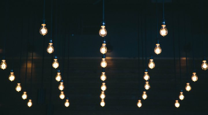 Edison bulbs hang from the ceiling of a dark room