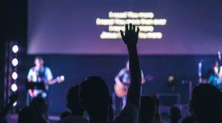 A man lifts his hands during a worship service