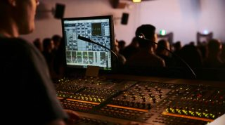 A man runs sound on an Avid SC48 Audio Console