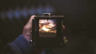 A man holding a camera looking through the viewfinder at a beautiful sunset