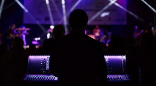A man stands behind a digital audio console at a concert with purple lighting in the background